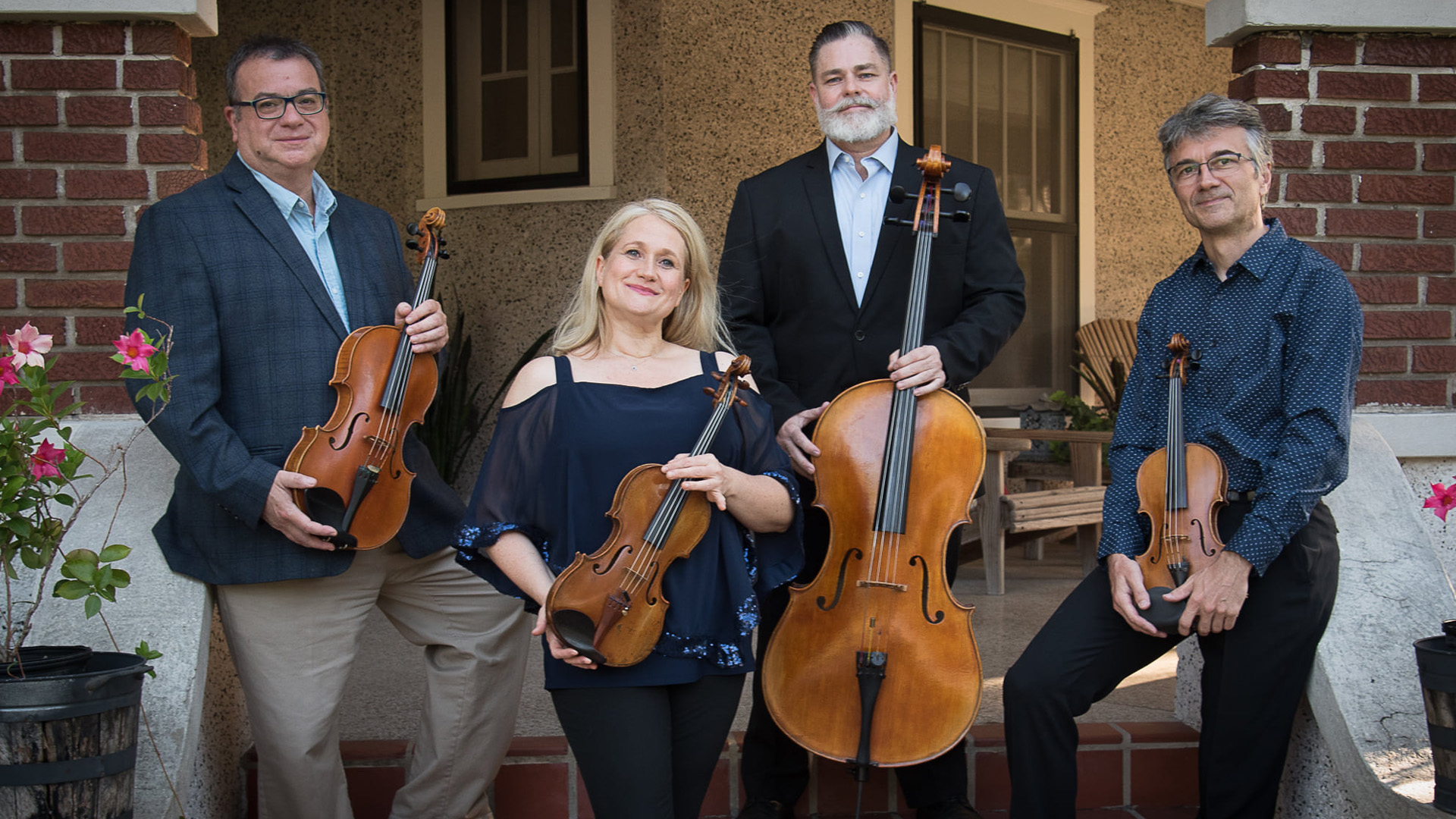 The four members of the Fernwood String Quartet pose in front of a house with their instruments. From left to right: Juan Carlos Siviero, viola; Julia Gessinger, violin; Hanrich Claassen, cello; Andreas Volmer, violin
