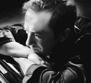 Multiple Grammy award-nominated jazz pianist Geoffrey Keezer rests his chin on both arms that are folded on top of one another.