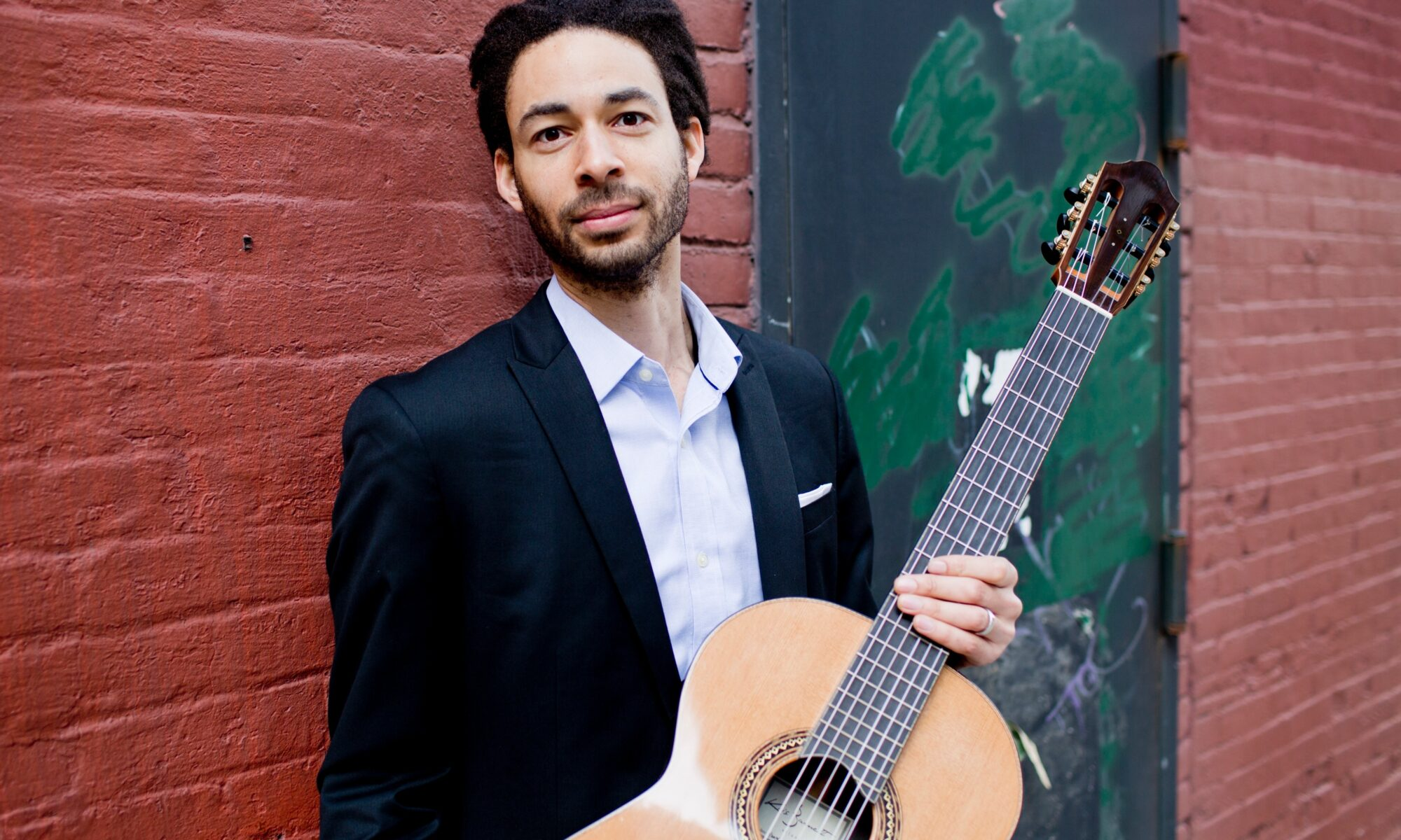 Classical guitarist Thomas Flippin stands in front of a brick wall while holding a guitar.