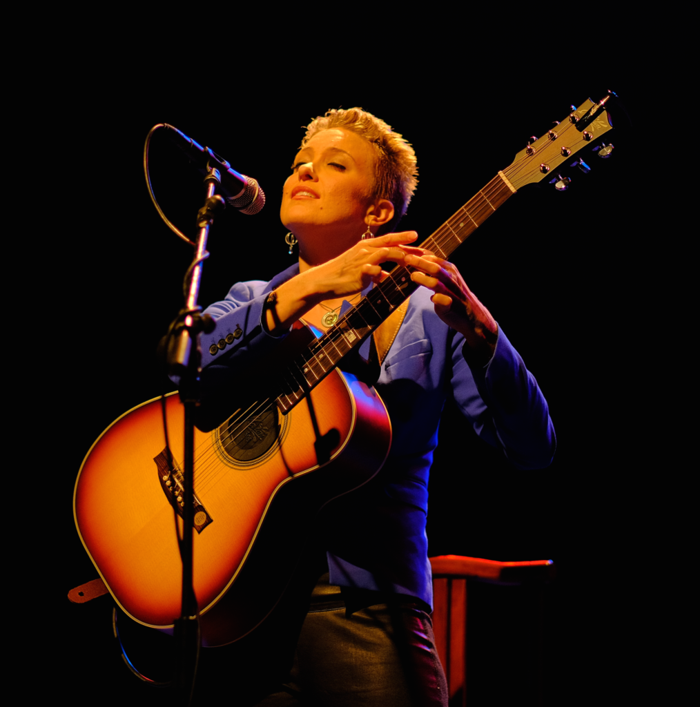 Fingerstyle guitarist Christie Lenée holds a guitar in both hands. Her right hand fingers tap into the strings of the guitar. She sings into the microphone.
