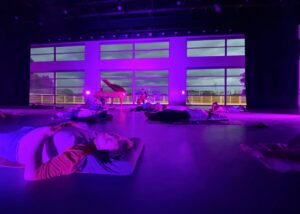 A group of people relax on yoga mats while musicians perform on piano and cello.